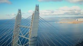 Auto het drijven bij kabel bleef brug over overzees op bewolkte hemel als achtergrond over stad stock video