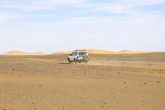 Auto het drijven in de woestijn van Ergchebbi in Marokko Stock Foto's