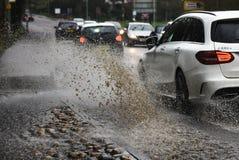 Auto 4 x 4 het drijven door Overstroomde weg bespattende stoep/bestratingen stock foto