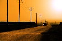 Auto het Drijven onderaan de Machtslijnen en Polen van Landwegkoplampen Stock Foto's