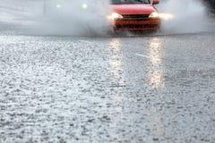 Auto het drijven op overstroomde weg met water het bespuiten van de wielen Royalty-vrije Stock Foto