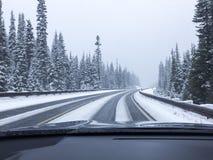 Auto het drijven op snow-covered sneeuwbergweg in de wintersneeuw Het gezichtspunt die van het bestuurders` s standpunt door wind stock foto's