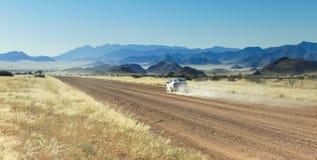 Auto het drijven snel met stofwolk op woestijnweg royalty-vrije stock afbeeldingen