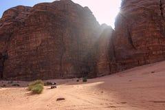 Auto het drijven toeristen door de Wadi Rum-woestijn, Jordanië, bij zonsondergang Royalty-vrije Stock Foto