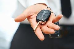 Auto het handel drijven en huurconceptenachtergrond Verkopershand die sleutels geven Stock Afbeelding