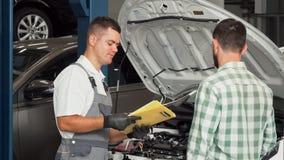 Auto het mechanische spreken aan de cliënt op automobiel de dienstcentrum stock video