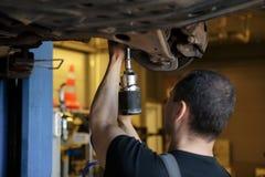 Auto het Mechanische Systeem van Fixing Tie Rod en van de Leiding terwijl het Zijn onder het Voertuig Autoonderhoud in de Beroeps stock foto's