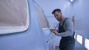Auto het oppoetsen, Autoschilders mannelijk schurend voertuig na verf met de hand bij verfkamer tijdens het reparatiewerk bij de  stock videobeelden