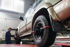 Auto hjuljustering i garage, SUV underhåll Fotografering för Bildbyråer
