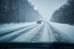 Auto im Sturm auf einer Winterstraße mit Verkehr Gefahr, die in Winter fährt Erste Personenansicht lizenzfreies stockfoto