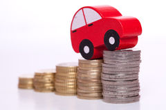 Auto industry. Red car over a lot of stacked coins Royalty Free Stock Image