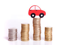 Auto industry. Red car over a lot of stacked coins Stock Images