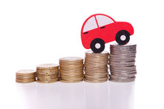 Auto industry progress. Red car over a lot of stacked coins Stock Image