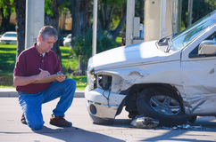 Auto insurance adjuster inspecting accident claim. Male auto insurance adjuster inspecting a vehicle that has been in an accident wreck Royalty Free Stock Photography