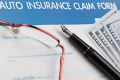 Auto insurance claim form. With fountain pen and dollar Stock Photo