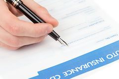 Auto insurance claim form. Male hand fills auto insurance claim form Royalty Free Stock Photo