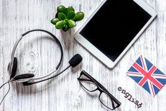 Auto-istruzione Apprendimento dell'online inglese Cuffie e PC della compressa sulla vista superiore del fondo di legno della tavo Fotografia Stock