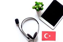 Auto-istruzione Apprendimento dell'online turco Cuffie e PC della compressa sul copyspace bianco del modello di vista superiore d Immagini Stock