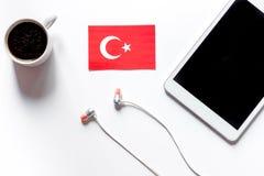 Auto-istruzione Apprendimento dell'online turco Cuffie e PC della compressa sul modello bianco di vista superiore del fondo della Fotografie Stock Libere da Diritti