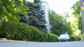 Auto lassen vorbei das junge Mädchen laufen, welches die Straße kreuzt stock video