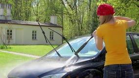 Auto lavagem manual mulher atrativa que lava o carro sujo com água exercida pressão sobre video estoque