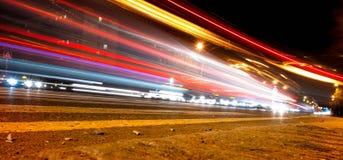 Auto lichte slepen op de straat dichtbij wegbrug, mensen die in snelle motie, de achtergrond van de nachtstraat lopen stock foto's