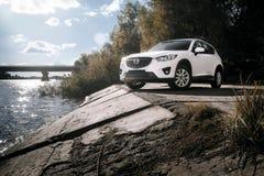 Auto Mazda CX-5 tribune op de weg van het asfaltplatteland dichtbij rivier bij dag Royalty-vrije Stock Afbeeldingen