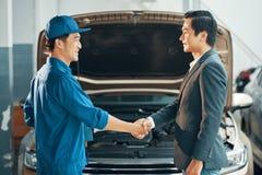 Auto mecânico e cliente que agitam as mãos foto de stock