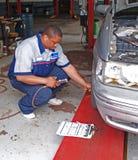 Auto mecânico que executa a inspeção da pressão de pneu Foto de Stock