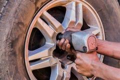 Auto mecânico que remove a roda com uma pistola pneumática para recaplitular Fotografia de Stock Royalty Free