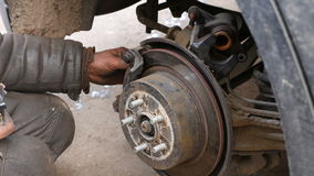 Auto mecânico que trabalha em freios na oficina de reparações do carro video estoque