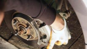 Auto mecânico que trabalha em freios em uma garagem doméstica da oficina de reparações do carro video estoque