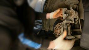 Auto mecânico que trabalha em freios em uma garagem doméstica da oficina de reparações do carro vídeos de arquivo