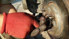 Auto mecânico que trabalha em freios em uma oficina de reparações do carro video estoque
