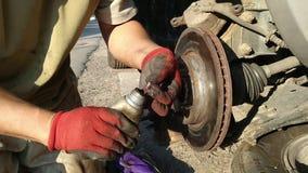 Auto mecânico que trabalha em freios em uma oficina de reparações do carro filme