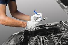 Auto mecânico que verifica o motor de automóveis na garagem imagens de stock