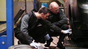 Auto mecânicos que mudam pneus de carro na oficina vídeos de arquivo
