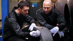 Auto mecânicos que reparam o pneu de carro com ruptura video estoque
