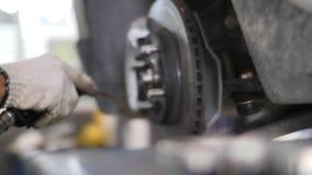 Auto mec?nico que trabalha em freios em uma garagem dom?stica da oficina de repara??es do carro filme