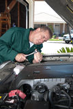 Auto mechanic. An auto mechanic uses a socket wrench to conduct maintenance and repair a car engine stock photography