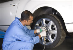 Auto mechanic. Removing the wheel of a car Royalty Free Stock Image