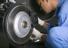 Auto mechanic. In blue uniform repairing brakes of a car Stock Images