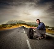 Auto mechanic. Portrait of auto mechanic with wheel on a country road royalty free stock images