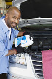 Auto Mechanic Adding Fluids To Minivan Royalty Free Stock Photos