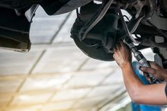Auto mechanic asian checking bush-bolt under double wishbone suspension by hand with tools car lift. Auto mechanic asian, checking bush-bolt, under double royalty free stock photo