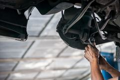 Auto mechanic asian checking bush-bolt under double wishbone suspension by hand with tools car lift. Auto mechanic asian, checking bush-bolt, under double royalty free stock images
