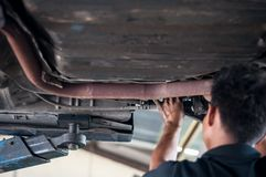 Auto mechanic asian checking bush-bolt under double wishbone suspension by hand with tools car lift. Auto mechanic asian, checking bush-bolt, under double royalty free stock photography