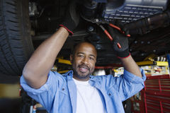 Auto Mechanic Beneath A Car. Portrait of a happy African American male mechanic beneath a car in garage Royalty Free Stock Photos