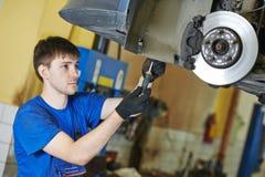 Auto mechanic at brake check Stock Photo