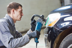 Auto mechanic buffing and polishing car headlight Royalty Free Stock Photo